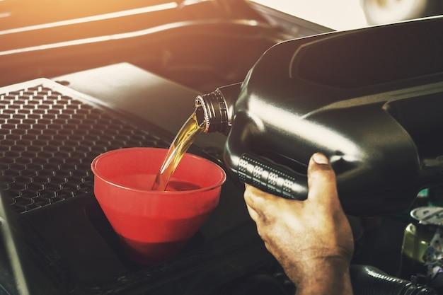 Автомеханик заменяет заливку масла в двигатель