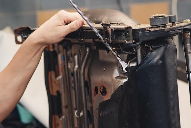 Руки автомеханика использует инструменты. рабочие руки мужчины в автосервисе, крупным планом.