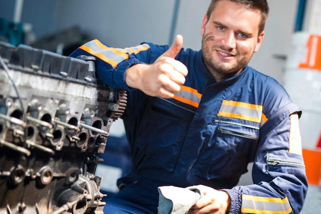 Car mechanic standing by the car engine with thumbs up.