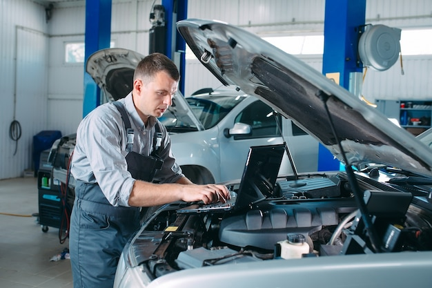 コンピューターのラップトップを使用して、修理および修理のために自動車のエンジン部品を診断およびチェックする自動車整備士