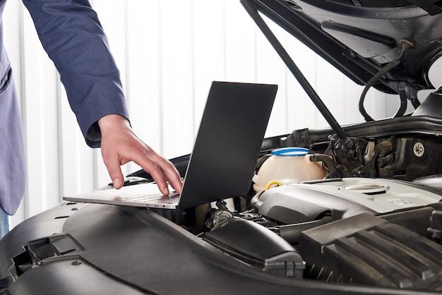自動車修理店でコンピューターを使用して自動車修理工
