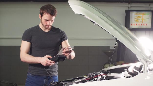 Автомеханик, использующий электроинструмент для проверки системы автомобиля при ремонте гаража
