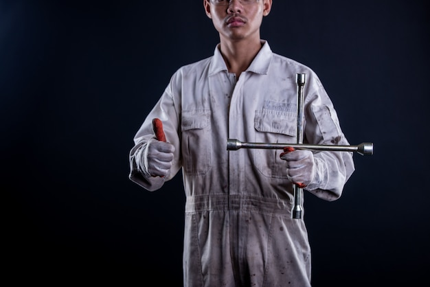 Car mechanic wearing a white uniform stand holding wrench