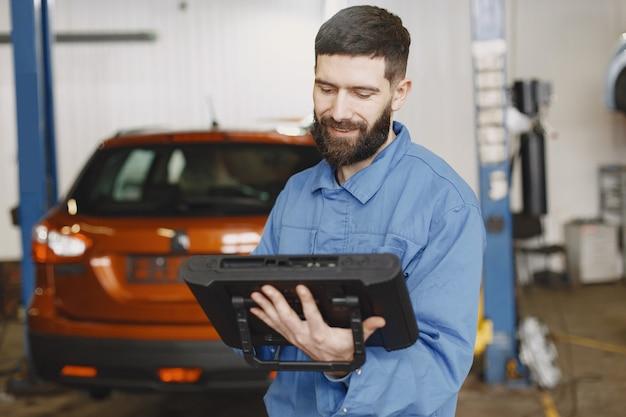 Meccanico di automobile con un tablet vicino all'auto in abiti da lavoro