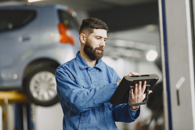Car mechanic with a tablet near car in work clothes