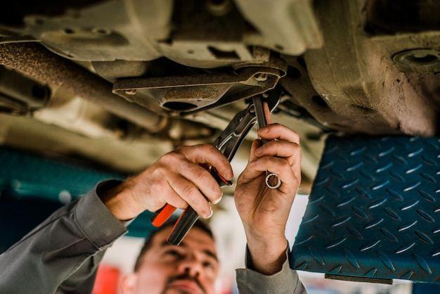 Car mechanic working on lifted car.