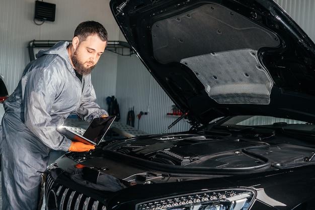Автомеханик, работающий с ноутбуком в авторемонтной службе, проверка двигателя автомобиля