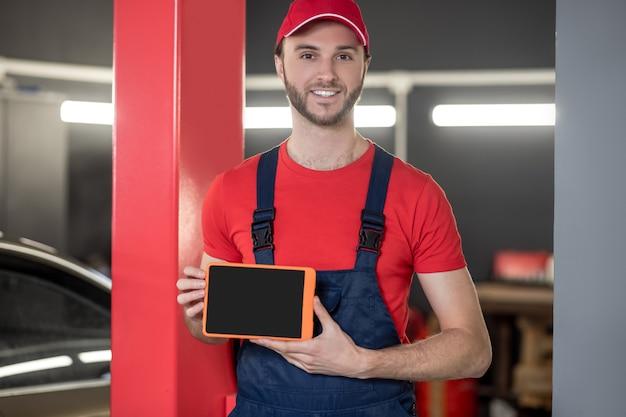 自動車整備士。青いオーバーオールと赤いtシャツの若い大人の笑顔の男が自動車修理店に立っているタブレット画面を示しています