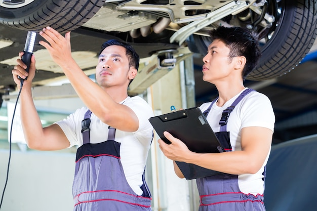 Car mechanics checking floor of luxury car on hoist