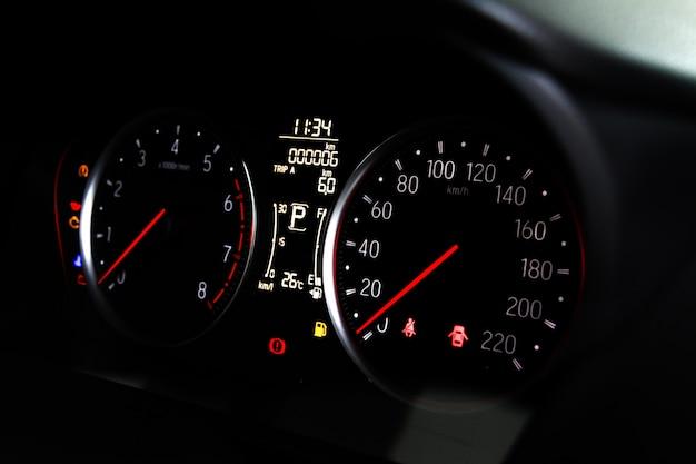 Автомобильные мили или спидометр, набравшие со значком и номером автомобиля на приборной панели.