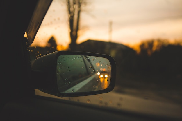 Car mirror with drops on sunset background. road in a travel