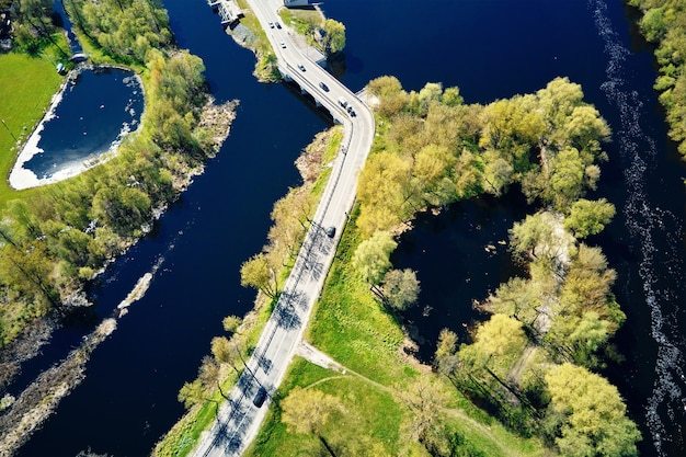 Car moving on the bridge over the river in european city, aerial view. bird eye view of small town landscape