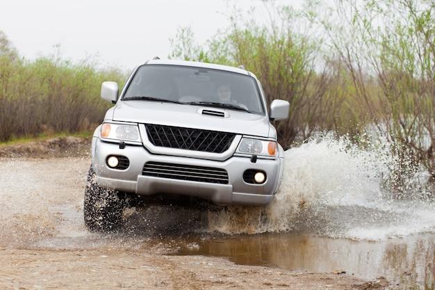 물 위를 달리는 자동차가 여성 운전자와 많은 물을 튀긴다