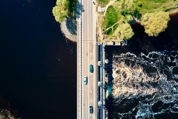 Автомобиль движется по мосту через реку в европейском городе с высоты птичьего полета