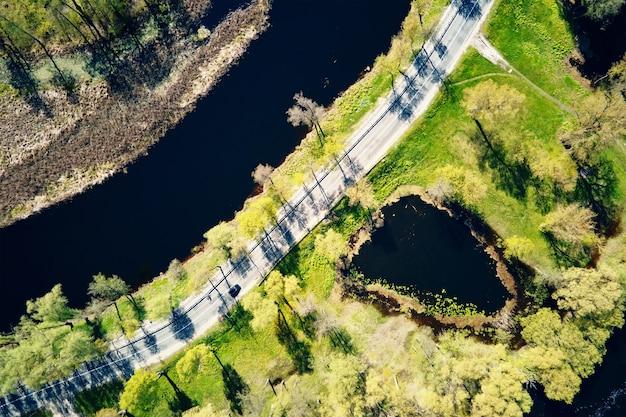 Автомобиль движется по дороге у реки в европейском городе с высоты птичьего полета на пейзаж небольшого городка