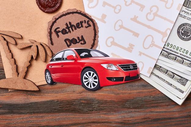 お金とカードの近くの車。ワックスシール付き封筒。贅沢な生活のための貴重なプレゼント。
