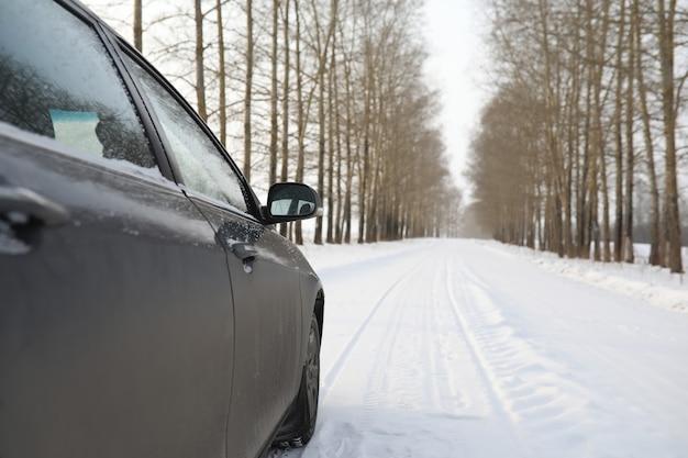 필드에 눈 덮인 겨울도로에 자동차.