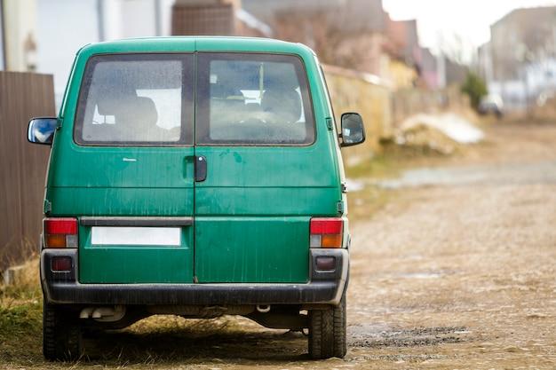 도시 거리에 차입니다. 도로 옆에 녹색 미니 버스가 주차되었습니다.