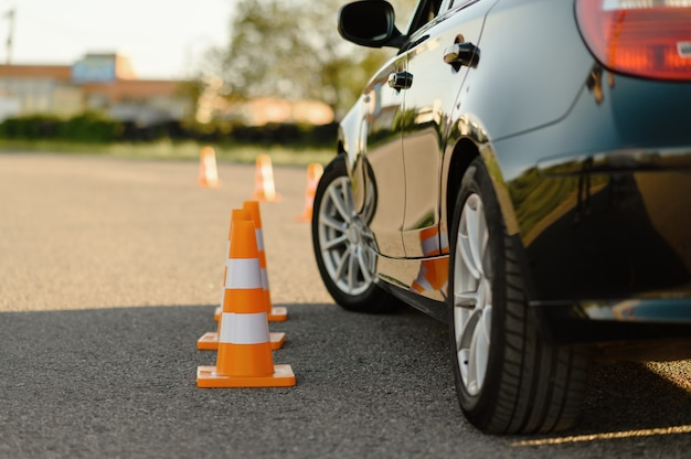 Car and orange traffic cones, lesson in driving school concept.