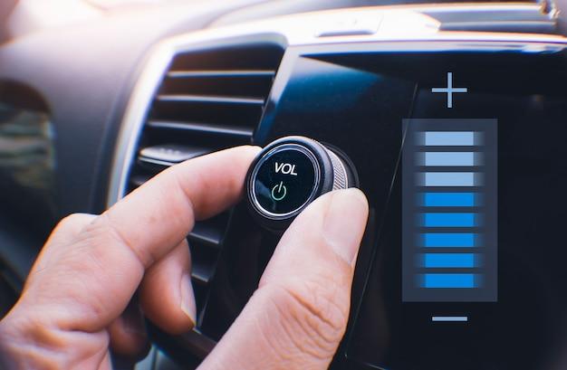 Владелец автомобиля рукой, поворачивая кнопку громкости автомобильной аудиосистемы в машине