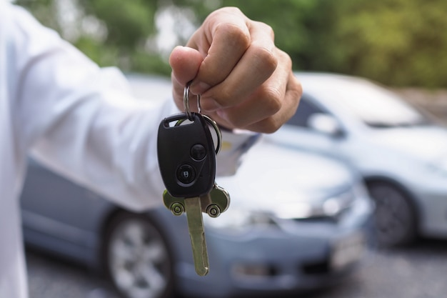 The car owner is standing the car keys to the buyer