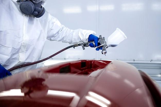 防護服を着た車の画家と、チャンバーワークショップでメタリックペイントとワニスを使ったマスク塗装の自動車バンパー。