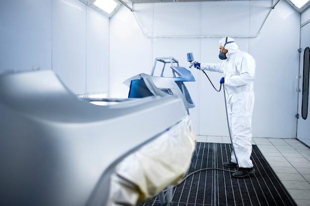 Автомобильный маляр в защитной одежде и маске, окрашивающий автомобильный бампер металлической краской и лаком в камерной мастерской.