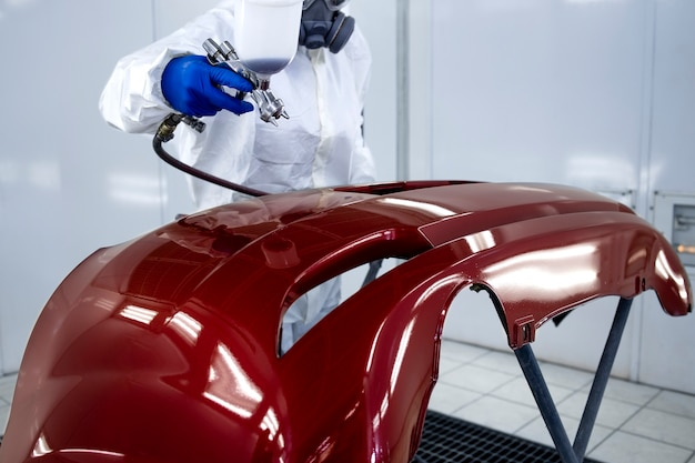 Car painter in protective clothes and mask painting automobile bumper with metallic paint and varnish in chamber workshop.