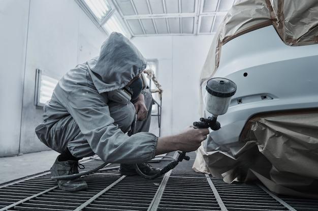 Покраска автомобилей и ремонт автомобилей. автомеханик в белом комбинезоне красит автомобиль распылителем аэрографа в покрасочной камере