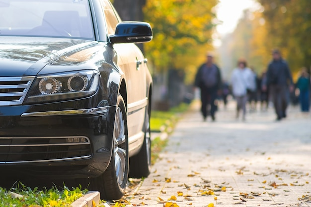 Car parked on a city street side on bright autumn day with blurred people walking in pedestrian zone