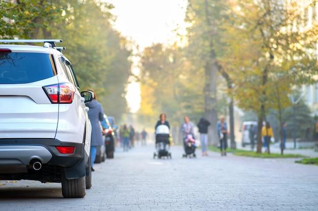 Автомобиль припаркован на обочине городской улицы в яркий осенний день с размытыми людьми, идущими по пешеходной зоне