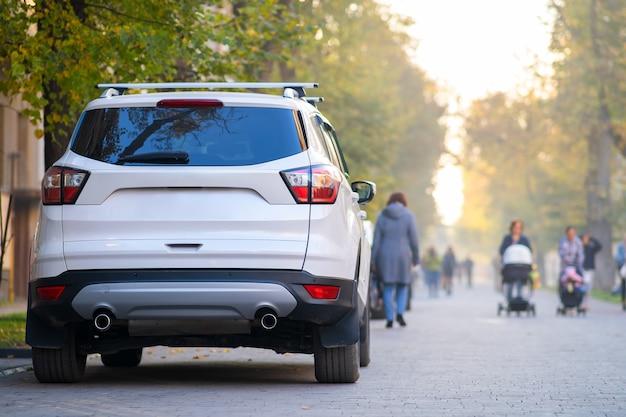 Автомобиль припаркован на стороне городской улицы в яркий осенний день с размытыми людьми, идущими по пешеходной зоне.