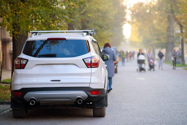Автомобиль припаркован на обочине городской улицы в яркий осенний день