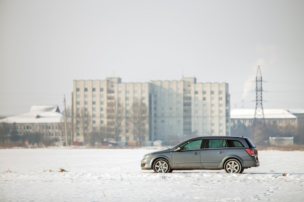 Car parked in snowy field on winter day.