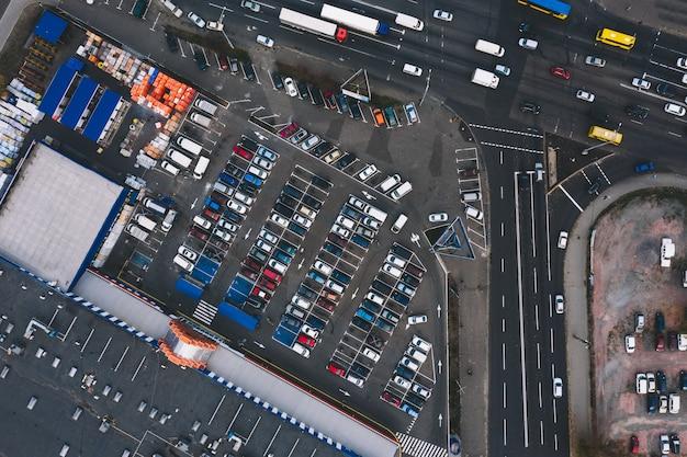 スーパーマーケットと車のトラックの近くのアスファルト駐車場の駐車場。異なるベニクルを持つ屋外駐車場。駐車場のコンセプト。