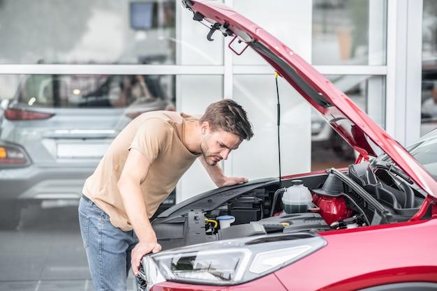 Автомобильные запчасти. озадаченный молодой взрослый мужчина в легкой футболке внимательно присматривается под открытым капотом красной машины на улице