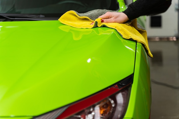 黄色のマイクロファイバークロスで車を磨きます。塗装の保護。