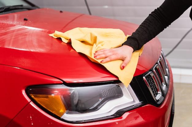 Полировка автомобиля салфеткой из микрофибры желтого цвета. защита лакокрасочного покрытия.