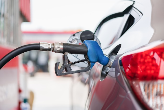 Car refueling with bule fuel nozzle at petrol station