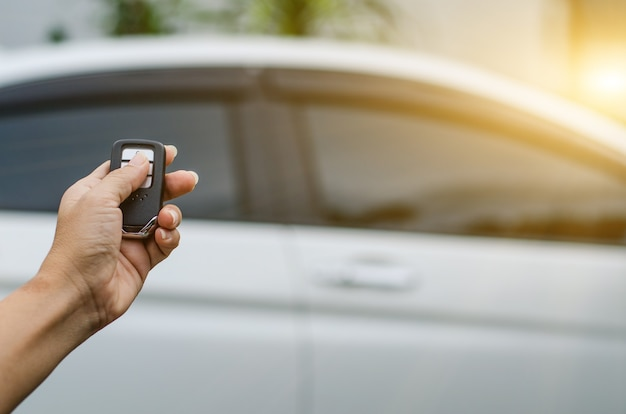 Car remote control by smart key, hand holding smart key to lock doors of white car