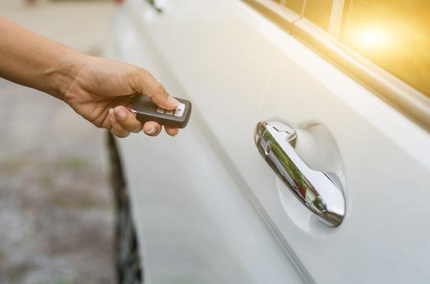 스마트 키에 의한 자동차 원격 제어, 흰색 자동차의 문을 잠그는 스마트 키를 들고 있는 손