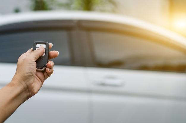 Пульт дистанционного управления автомобилем с помощью смарт-ключа, рука держит смарт-ключ для блокировки дверей белого автомобиля