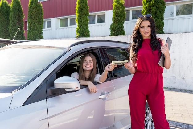 2人の美しい女性の間のレンタカー取引