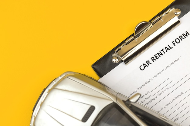 Car rental form. clipboard with rental agreement. car toy of office desktop, yellow background. top view photo