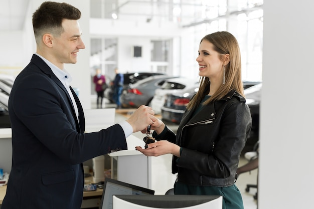 Car rental and insurance concept, young salesman receiving money and giving car's key to customer after sign agreement contract with approved good deal for rent or purchase.