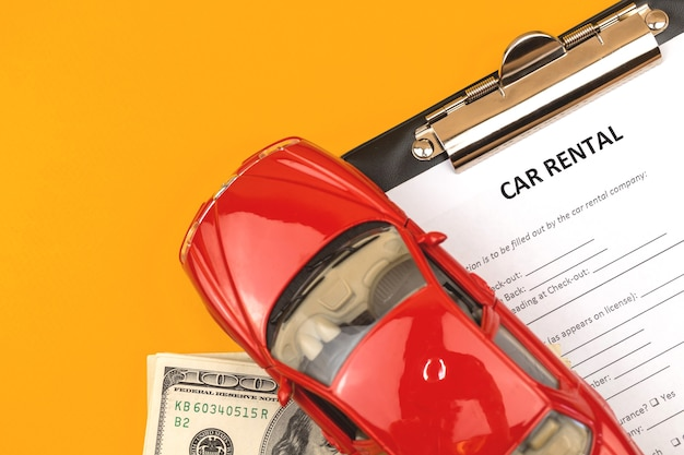 Car rental lease contract form. office desk with clipboard and toy car. copy space photo