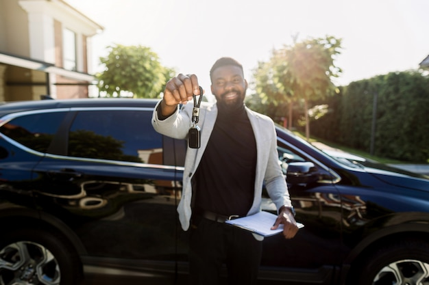 Car rental service. happy african man salesmanager or client holding key and smilikng near new black car. focus on key
