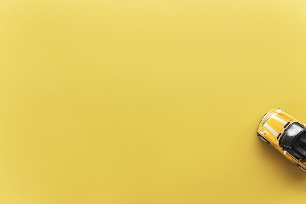 자동차 렌탈, 여행, 여행 또는 주말 활동 개념 평면 노란색 배경에 노란색 작은 장난감 쿠페 형 자동차와 함께 누워