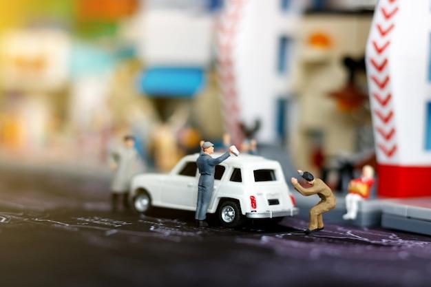 Car repair concept. miniature car mechanic working in auto repair service station.