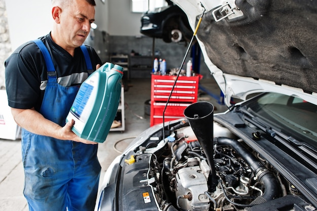Car repair and maintenance theme. mechanic in uniform working in auto service, pouring new motor oil.
